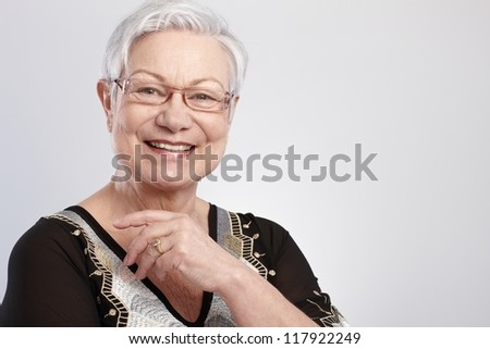 Closeup portrait of smiling elderly lady in glasses.