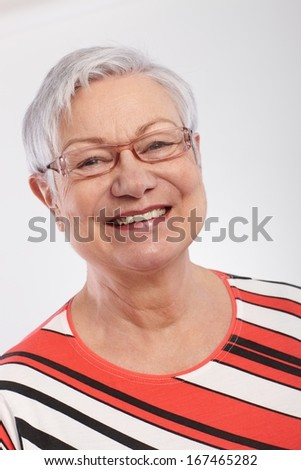 Closeup portrait of smiling old lady in stripy top.