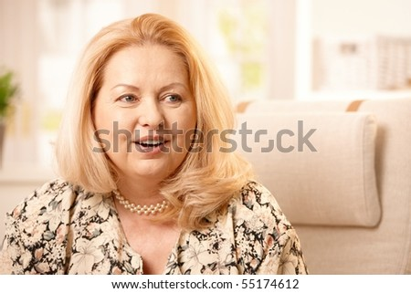 Closeup portrait of smiling senior woman with long blond hair talking.?