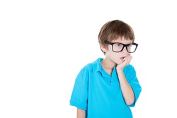 Closeup portrait of smiling smart adorable young boy in blue shirt with big black glasses thinking daydreaming about something serious chin on hand, isolated on white background, copy space to left