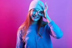 Closeup portrait of smiling teenager girl posing against pink neon wall and covering her eye with ok sign, woman wearing sweater and hat, expresses positive emotions, looks satisfied. People concept