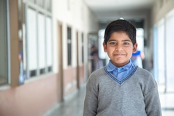 Closeup portrait of smiling 6-7 years Indian kid, standing straight at school campus in school uniform and looking at camera