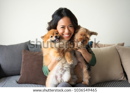 Closeup portrait of smiling young attractive woman looking at camera, sitting on sofa and holding Yorkshire terrier and Pomeranian spitz at home. Pets concept. Front view.