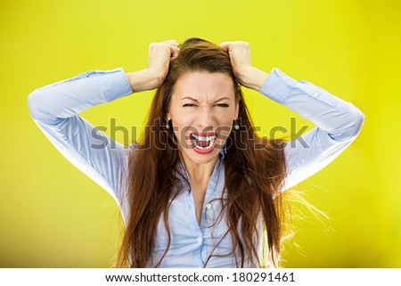 Closeup portrait of stressed business woman, pulling her hair out yelling screaming with temper tantrum isolated on yellow, green background. Negative human emotion facial expression reaction attitude