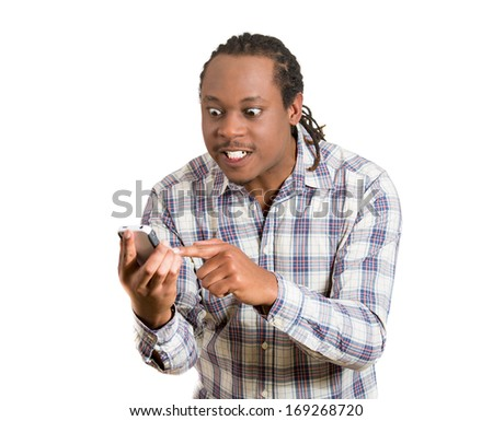 Closeup portrait of surprised, shocked displeased angry young man who is not happy by what he sees on his cell phone, isolated on white background. Negative human emotion facial expression feelings