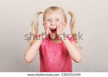 Closeup portrait of surprised white blonde Caucasian preschool girl making faces in front of camera. Child smiling laughing posing in studio on plain light background. Kid expressing emotions