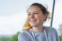 Closeup portrait of teenage girl of 14, 15 years old in gray sweatshirt. Background blue sky in clouds, copy space, place for text, back to school