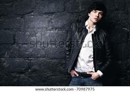 Closeup portrait of the beautiful young sexual man in a leather jacket, on a black background