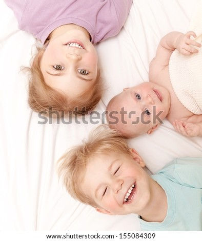 Closeup portrait of three cheerful kids lying down at home, newborn baby with brother and sister, happy family, love and friendship concept