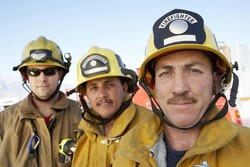 Closeup portrait of three fire fighters in helmets against sky