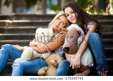 Closeup portrait of two beautiful girls sitting on stairs with teddy bears