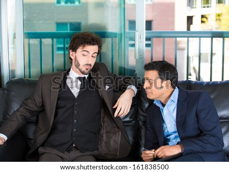 Closeup portrait of two guys in business suits sitting on black couch. One is crying about life problems and other probably caused the trouble or is indifferent. Human emotions and communication