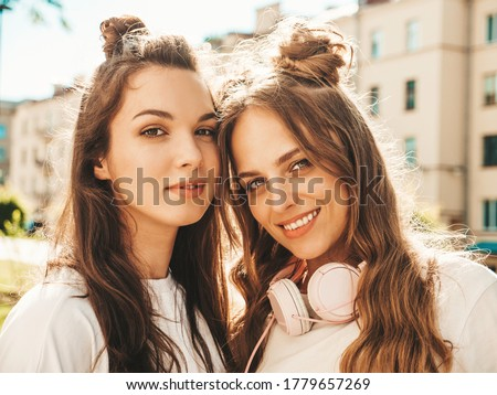 Closeup portrait of two young beautiful smiling hipster women in trendy summer white t-shirt clothes.Sexy carefree women posing on street background. Positive models looking at camera. Beauty concept