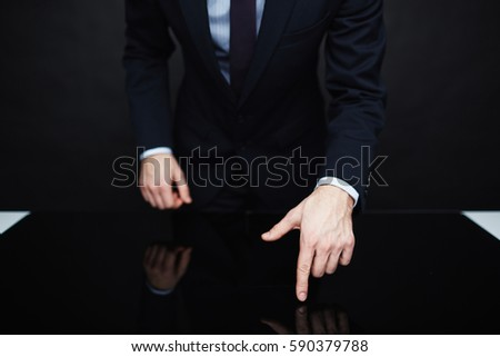 Closeup portrait of unrecognizable authority figure wearing business suit standing leaning on table  making persuasive hand gesture against black background Foto stock ©