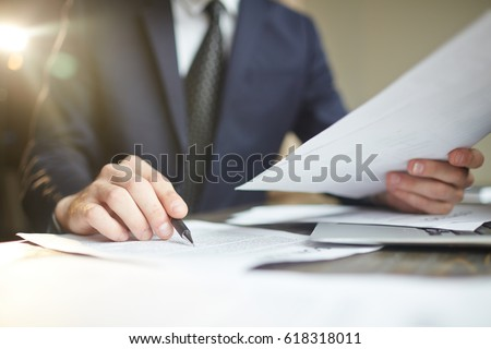 Closeup portrait of unrecognizable successful businessman wearing black formal suit reading documents at desk with laptop, busy with paperwork
