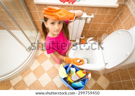 Closeup portrait of upset tired girl cleaning toilet with brush