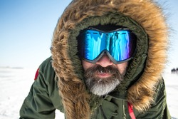 Closeup portrait of winter adventurer over sky and snow background. Active healthy sport lifestyle