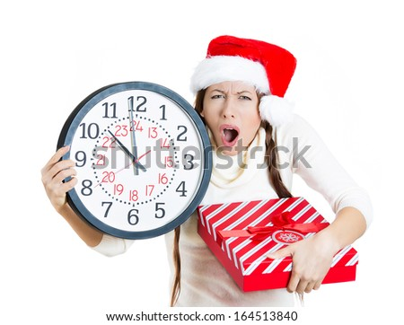 Closeup portrait of worried, stressed young woman wearing red santa claus hat, holding clock and a gift box, isolated on white background. Emotion, facial expression. Last minute christmas shopping