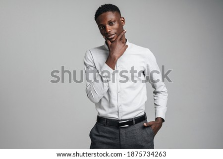 Closeup portrait of young african man thinking deeply about something isolated on gray background ストックフォト ©