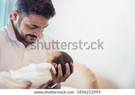 Closeup portrait of young asian Indian father holding his newborn baby with copy space. Healthcare and medical daycare nursery love lifestyle together single dad father's day holiday concept
