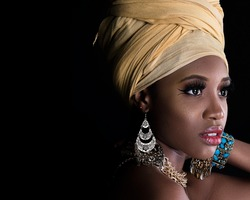 Closeup portrait of young Beautiful African-American female model with beautiful eyes looking away wearing traditional ethnic clothes standing on dark background