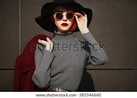 Closeup portrait of young beautiful fashionable woman with sunglasses. Lady posing on dark grey background. Model wearing stylish wide-brimmed hat. Girl looking at camera. Female fashion.Toned