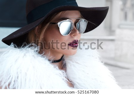 Closeup portrait of young beautiful fashionable woman with sunglasses. Lady posing on dark grey background. Model wearing stylish wide-brimmed hat, jacket. Girl looking at camera. Female fashion.Toned #525167080