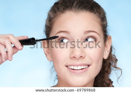 Closeup portrait of young beautiful girl with perfect skin and curly hair. Mascara make up by brush