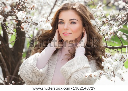 Closeup portrait of young beautiful woman outdoors in spring flowers. Beauty girl. Perfect make up. Blond lady with long curly hair.