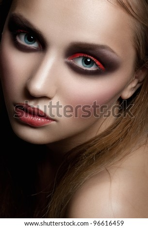 Closeup portrait of young beautiful woman with bright fashion makeup