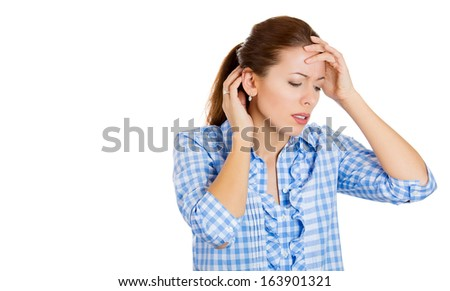 Closeup portrait of young beautiful woman with hands on head and neck thinking about something making her sad looking downwards, isolated on white background space to left. Negative human emotion