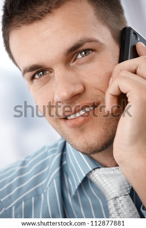 Closeup portrait of young businessman using mobile phone, smiling.
