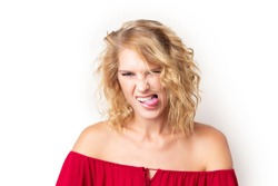 Closeup portrait of young caucasian woman with disgusted face expression isolated at white background. Irritated girl is showing grimace touching teeth with toungue.