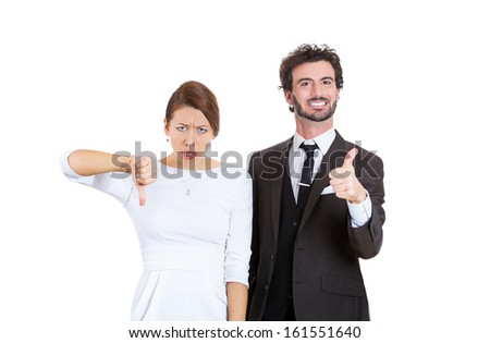 Closeup portrait of young couple, man and woman ; one being excited, smiling, showing thumbs up, other serious, concerned, unhappy showing thumbs down, isolated on white background. Emotion contrasts
