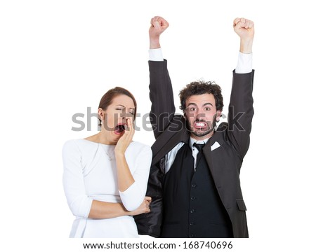 Closeup portrait of young couple, man, woman. One being excited, happy smiling, optimistic, other bored, serious, sleepy, showing no interest, isolated on grey background. Emotion, feelings contrasts.