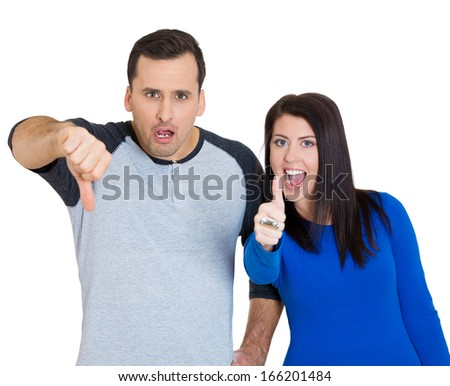 Closeup portrait of young couple, man, woman. One being excited happy smiling, showing thumbs up, other serious, concerned, unhappy showing thumbs down, isolated on white background. Emotion contrasts