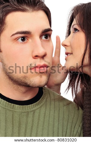 Closeup portrait of young couple of students. Woman whispering something to her boyfriend. He is surprised. - stock photo