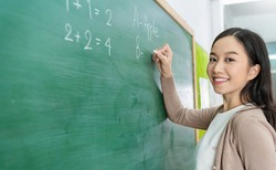 Closeup portrait of young happy asian teacher write on chalk board. Woman writing on blackboard wall. Idea creative education teaching math and spelling letter, knowledge, back to school concept