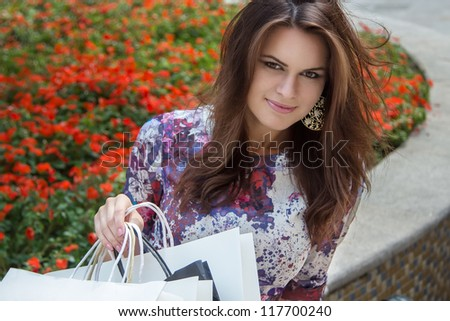Closeup portrait of young joyful woman with shopping bags in the park. Smiling cheerful woman