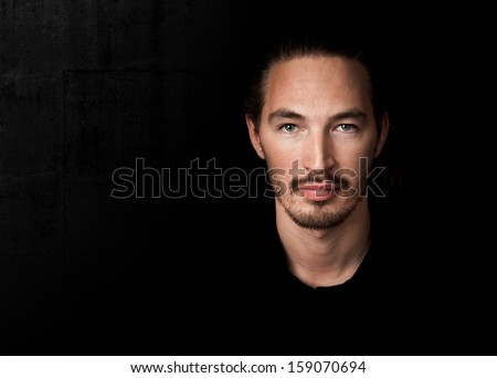 Closeup portrait of young man above black wall background
