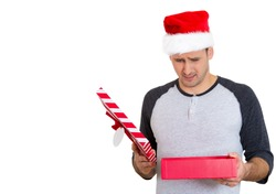 Closeup portrait of young man in red santa claus hat opening gift, very upset at what he received, isolated on white background. Negative emotion, facial expression feeling. Holiday shopping concept