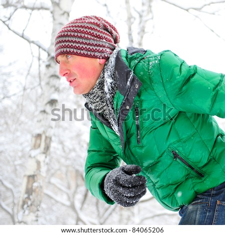 Closeup portrait of young man running in winter park wearing sportswear and looking forward