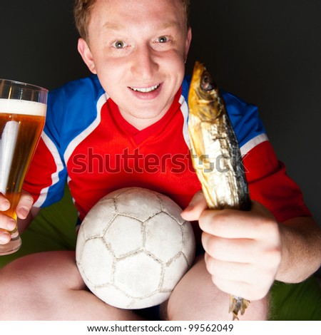 Closeup portrait of young man wearing sportswear fan of football team is watching tv and rooting for his favorite team. Sitting on beanbag alone at night drinking beer and eating fish.