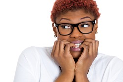 Closeup portrait of young nerdy funny female, unhappy scared woman with black glasses biting nails looking away craving for something, anxious, worried, isolated on white background. Face expressions