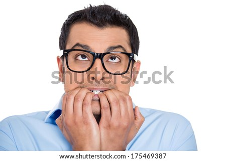 Closeup portrait of young nerdy unhappy scared man, student with black glasses biting nails looking up with a craving for something, anxious, worried, isolated on white background. Face expression