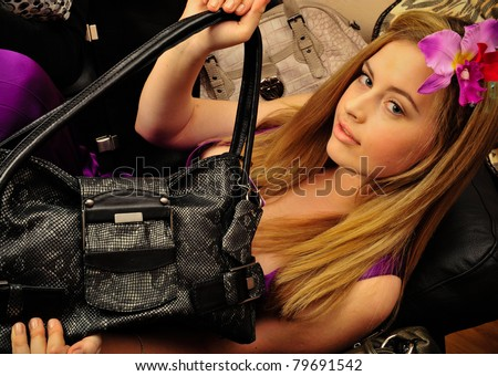 Closeup portrait of young pretty lonely woman laying on sofa indoors and holding her luxury handbag