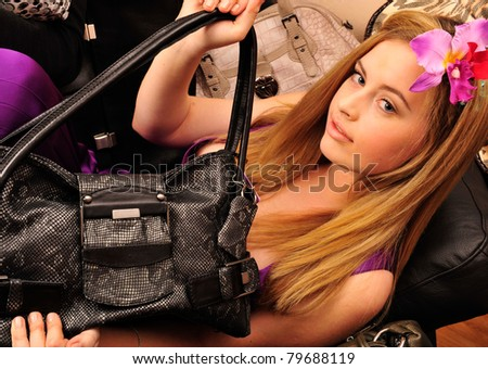 Closeup portrait of young pretty lonely woman with her handbags