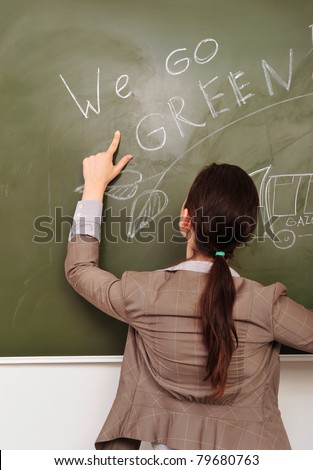 Closeup portrait of young pretty woman wearing formal suit erasing gasoline smoke on green board. Ecology care concept