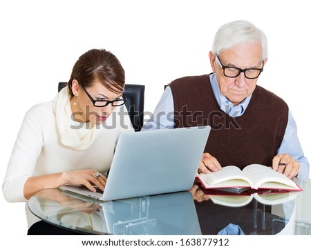 Closeup portrait of young pretty woman working on laptop and older senior mature grandpa man reading from book on table, isolated on white background. Generation differences and gap technology concept