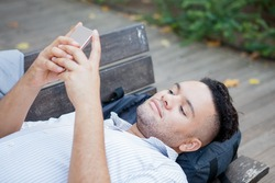 Closeup portrait of young relaxed student lying on bench in park with backpack under head and texting message to his girlfriend. Life balance concept